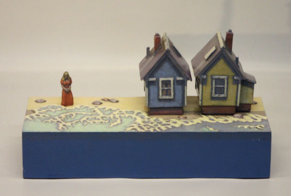 sculpture of houses and a woman on the beach