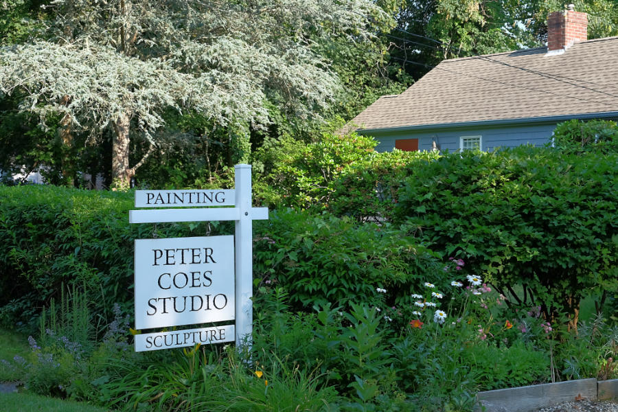 White sign in front of plantings and building